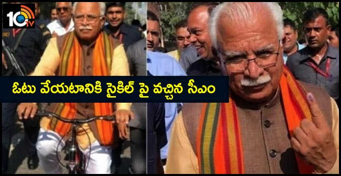 Haryana Chief Minister Manohar Lal Khattar rides a cycle to the polling booth