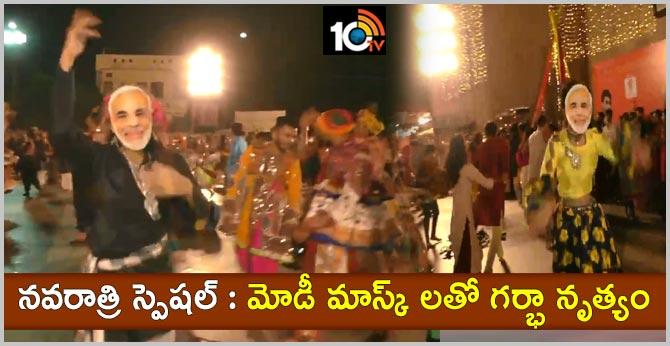 People play garba wearing masks of PM Narendra Modi, in Surat
