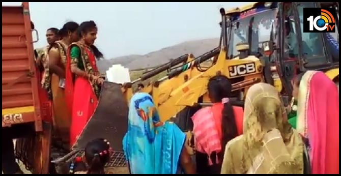 a video showing women taking help from the JCB machine to climb off a truck
